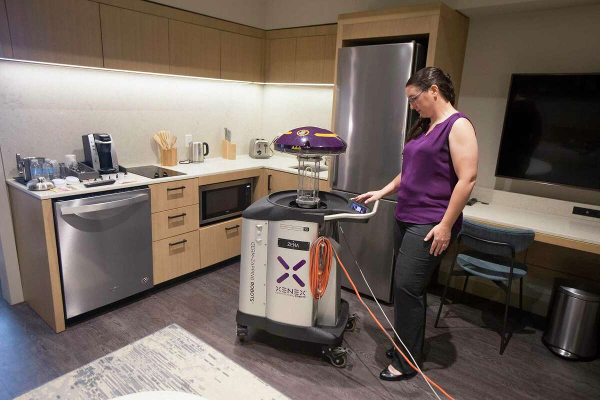 Dr. Sarah Simmons, senior director of science for Xenex Disinfection Services demonstrates one of the two germ-fighting cleaning robots being used at The Westin Houston Medical Center to sanitize and disinfect guest rooms and common areas against the threat of coronavirus Wednesday, March 11, 2020, in Houston.