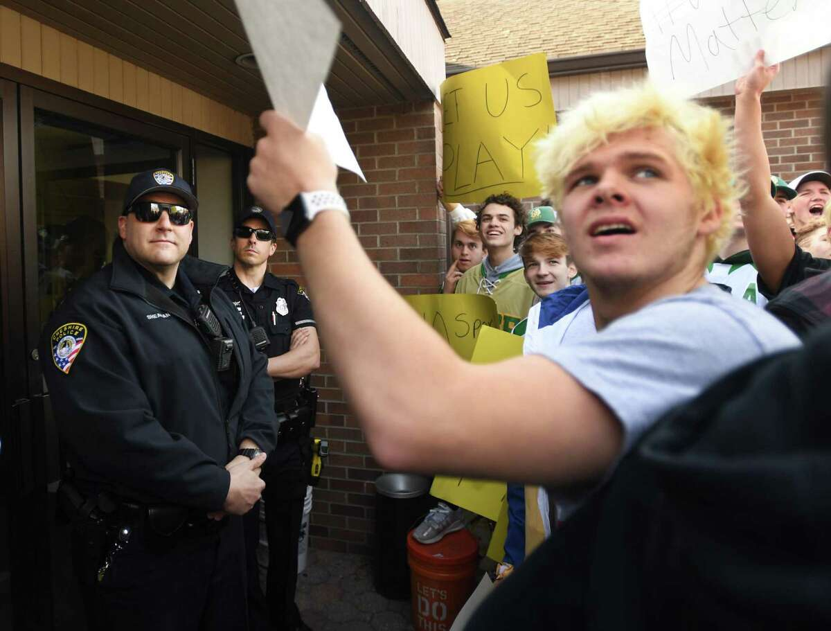 Cheshire police block the front doors of CIAC offices in Cheshire, Conn. as student athletes, including Pomperaug senior swimmer Jack Shay, right, of Southbury, protest over the cancelling of state playoffs and tournaments in the wake of the coronavirus on Wednesday, March 11, 2020.