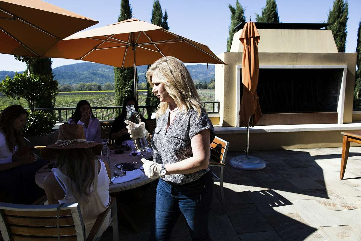 Victoria Acquistapace, wine educator at the Round Pond tasting room wearing gloves as a precautionary measure to protect the spread of the coronavirus as she pours water for customers at the Round Pond tasting room, Rutherford, California, March 11th, 2020. Napa Valley wineries are seeing a downturn in corporate group visits due to coronavirus concerns. At the same time, these wineries are open for business and are taking extra precautions to be sanitary.