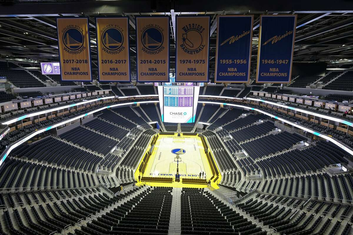 FILE - In this Aug. 26, 2019, file photo, the Golden State Warriors championship banners hang above the seating and basketball court at the Chase Center in San Francisco. Officials have banned large gatherings and events in the Seattle metro area and in San Francisco to try to stop the spread of the new coronavirus. Wednesday, the San Francisco mayor banned gatherings of 1,000 or more people, including Golden State Warriors games. For most people, the new coronavirus causes only mild or moderate symptoms. For some it can cause more severe illness, especially in older adults and people with existing health problems.(AP Photo/Eric Risberg, File)