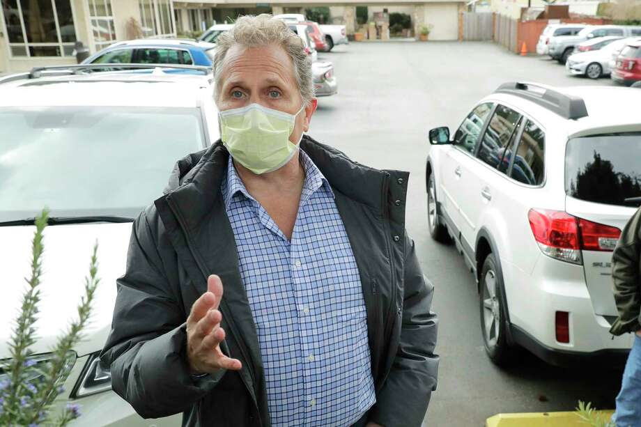 Scott Sedlacek, who says he has tested positive for the COVID-19 coronavirus, wears a mask as he talks to reporters near the parking lot of the Life Care Center in Kirkland, Wash., Wednesday, March 11, 2020, near Seattle after he visited his father, Chuck Sedlacek, 86, who is also positive for the virus and is a patient in the nursing home, which is at the center of the outbreak of the COVID-19 coronavirus in Washington state. For most people, the new coronavirus causes only mild or moderate symptoms. For some it can cause more severe illness.(AP Photo/Ted S. Warren) / Copyright 2020 The Associated Press. All rights reserved.