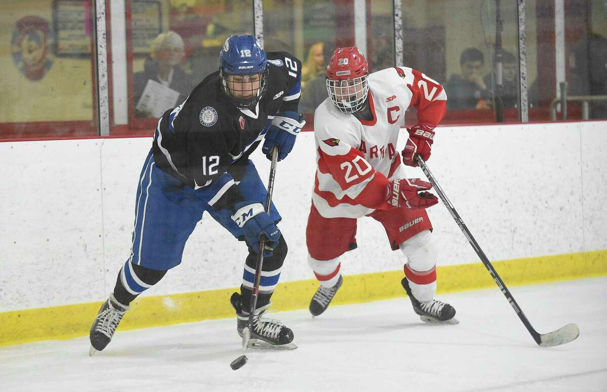 Darien Max Sharp (12) plays the puck off the boards under pressure from Greenwich's Michael Connerty (20) in the second period of an FCIAC Boys Hockey semifinal game at Hamill Rink on March 4, 2020 in Greenwich, Connecticut.