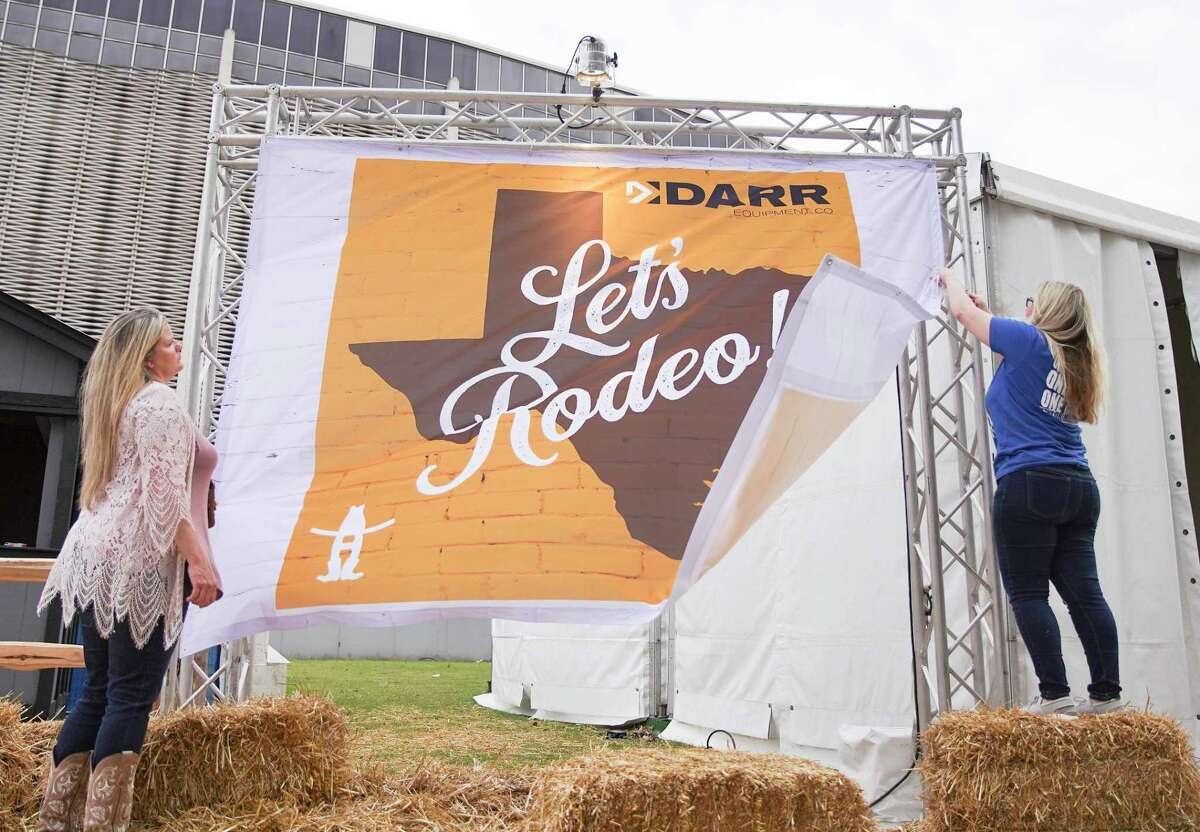 Chele Summers, left, and Amber Hood of Darry Equipment Co., take down their sign after the Houston Livestock Show and Rodeo closed early on Wednesday, March 11, 2020.