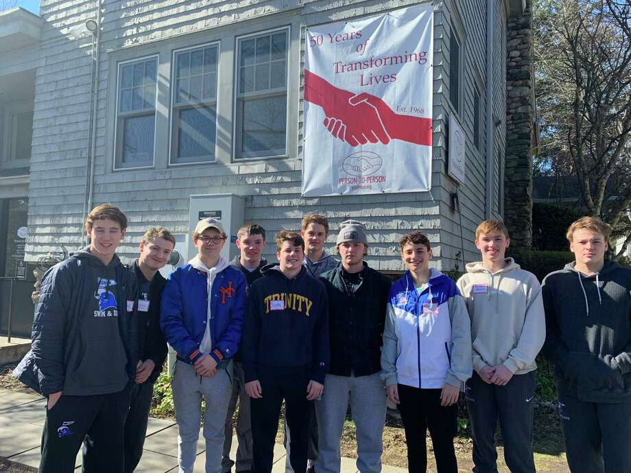 Members of the Darien boys swimming and diving team recently volunteered their time at Person-to-Person at St. Luke's Church in Darien in February. From left, Jack Stobbie, John Barsanti, Griffin Trygg, Harry FitzPatrick, co-captain Scotty Tuck, Davis Tuzinkiewicz, Drew Major, Victor Coelho, Christian Davidson, and Will Doran. Photo: Contributed / Hearst Connecticut Media / Hearst Connecticut Media
