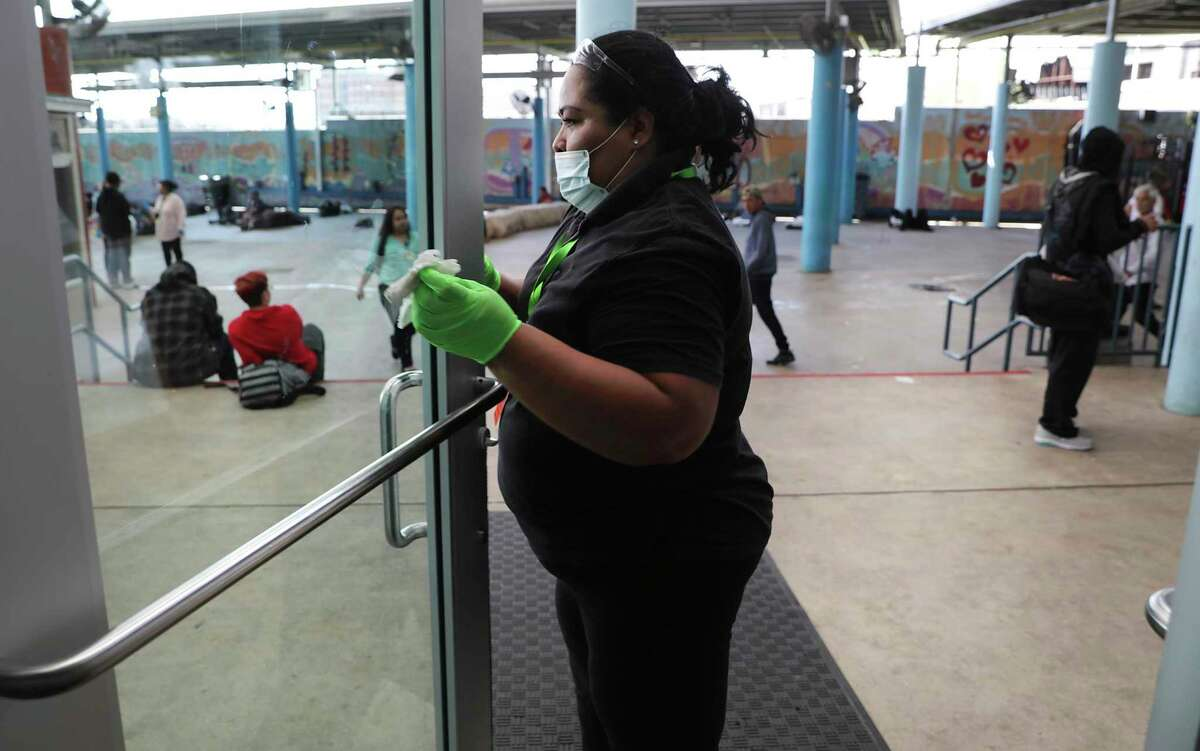 Barbara Lopategui cleans a glass door at Haven for Hope on Wednesday. The shelter is taking precautions to keep the area and clients free of coronavirus.