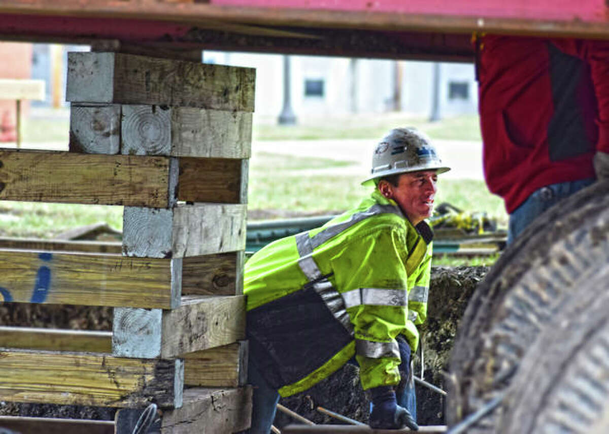An EHMMidwest worker gages space between settling blocks and the floor of the Nickel Plate building as the process of moving the building closer to the entrance of the Lewis and Clark Community College N.O. Nelson campus in Edwardsville began on Wednesday.