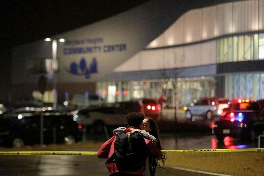 Jaylen Greenlee embraces his friend Becca Johnson outside the Maryland Heights Community Center on Monday, Feb. 24, 2020, after a gunman entered the complex and fired shots, killing at least one. Authorities say a part-time janitor killed a co-worker at the Maryland Heights Community Center in St. Louis before a police officer rushed inside and exchanged gunfire with the shooter. The gunman was seriously wounded. (Christian Gooden/St. Louis Post-Dispatch via AP)