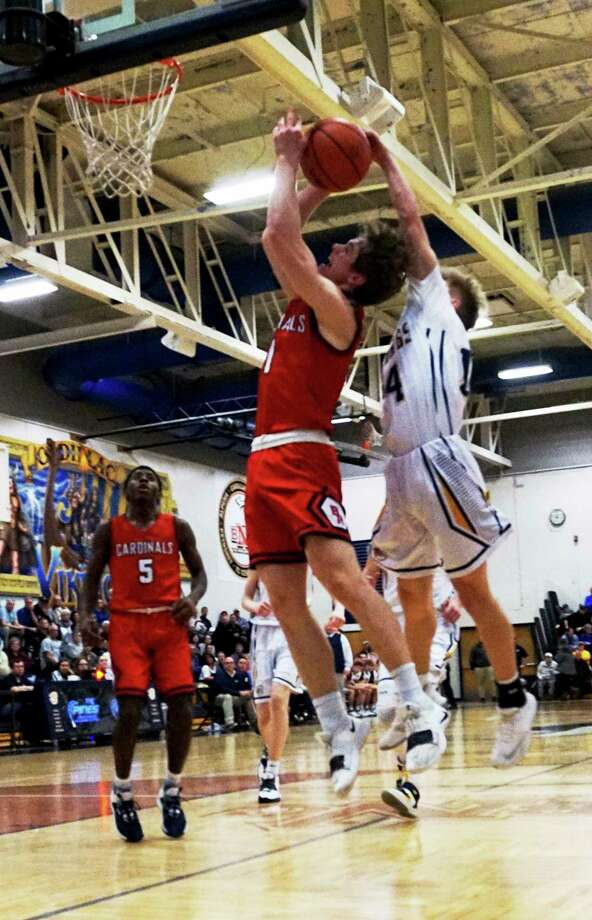 Big Rapids junior Sam Alley is fouled by Cadillac junior Brady McLaurin during BR's loss in the semifinal game on Wednesday night at Cadillac High School. (Pioneer photo/Joe Judd)