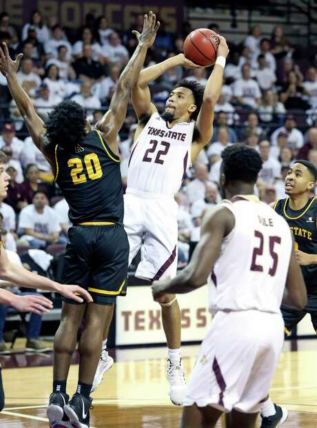 Bobcat guard Nijal Pearson goes up to loft a jumper over Adrian Delph as Texas State plays Appalahian State in the opening conference tournament basketball game on Feb. 11, 2020.