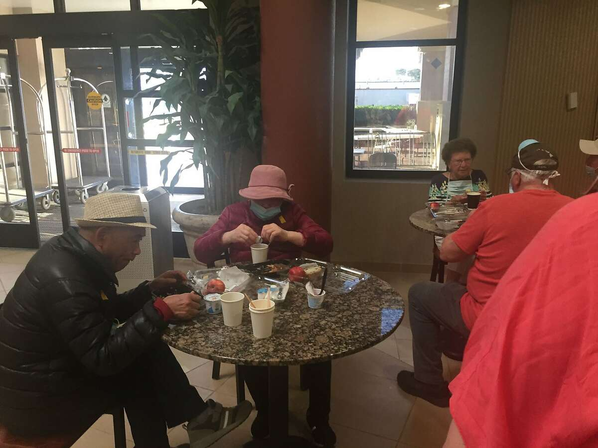 People eat with no masks in common areas at the quarantine site on Travis Air Force Base. A group of Grand Princess passengers are under 14-day quarantine there.