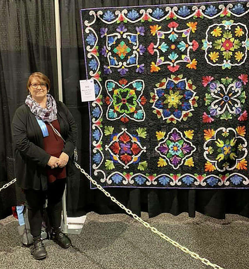 Rosanne Hamilton of Chapin stands next to her award-winning quilt as it is displayed at the American Quilters Society Show in Daytona Beach, Florida. Hamilton's quilt was among 235 chosen from entries from North America, Europe, Asia, South American and Australia. It was her first attempt at entering an international contest. Photo: Photo Provided