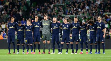Real Madrid's players observe a minute of silence for former Betis player Manuel Regatero before the Spanish league football match between Real Betis and Real Madrid CF at the Benito Villamarin stadium in Seville on March 8, 2020. (Photo by CRISTINA QUICLER / AFP)