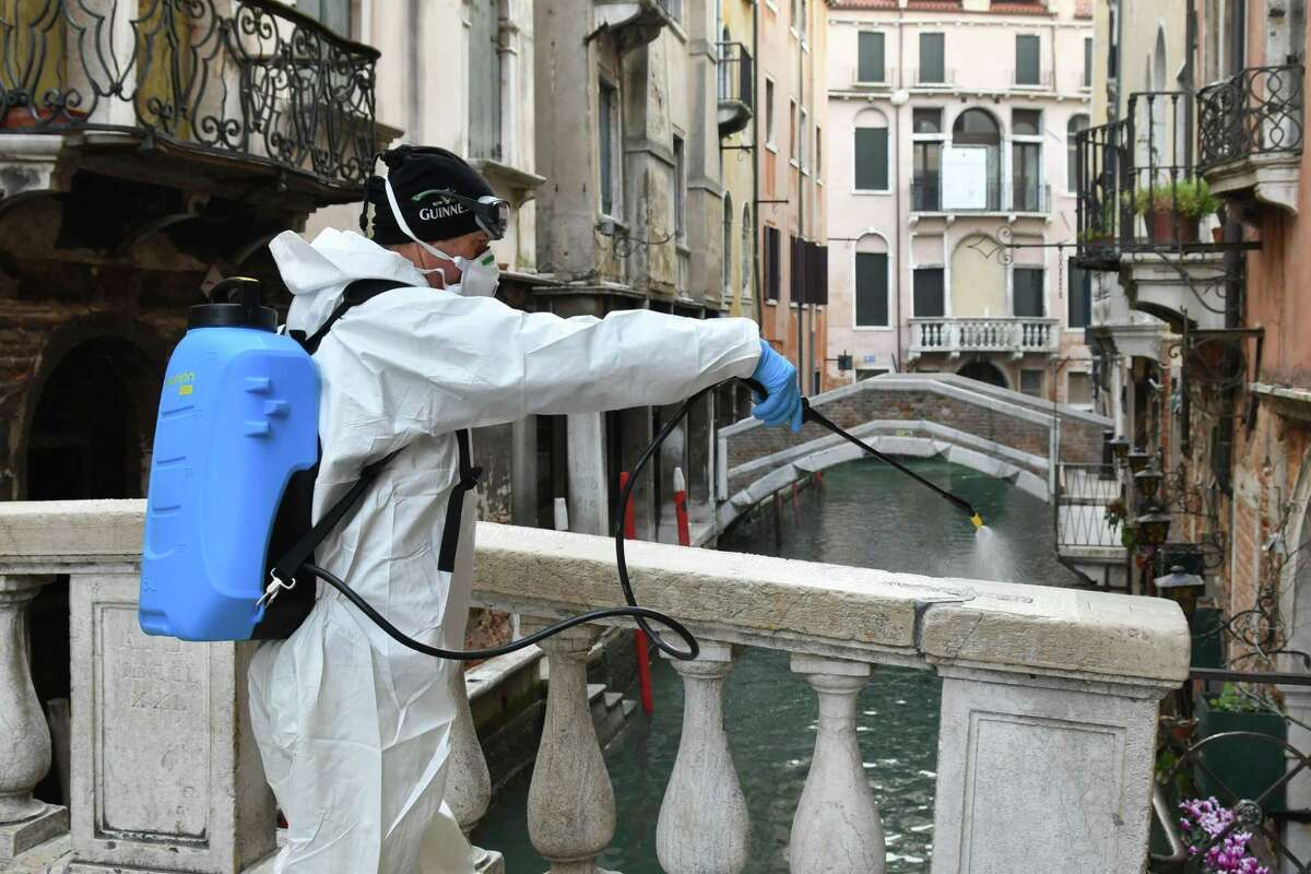 A worker sprays disinfectant in public areas in Venice this month, a day after Italy imposed unprecedented national restrictions on its 60 million people Tuesday to control the deadly COVID-19 coronavirus.