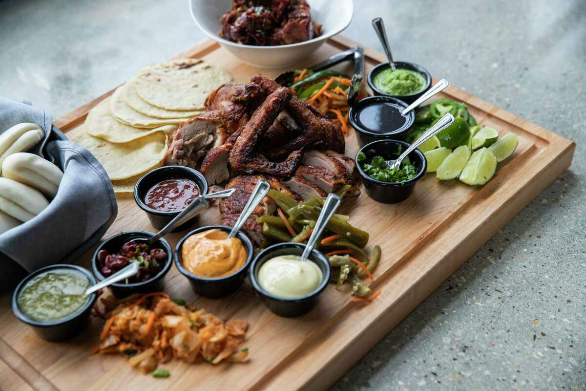 Woodshed Smokehouse's What the Duck platter of smoked and roasted duck, pickled veggies, kimchi, Korean barbecue sauce, steamed buns, tortillas and