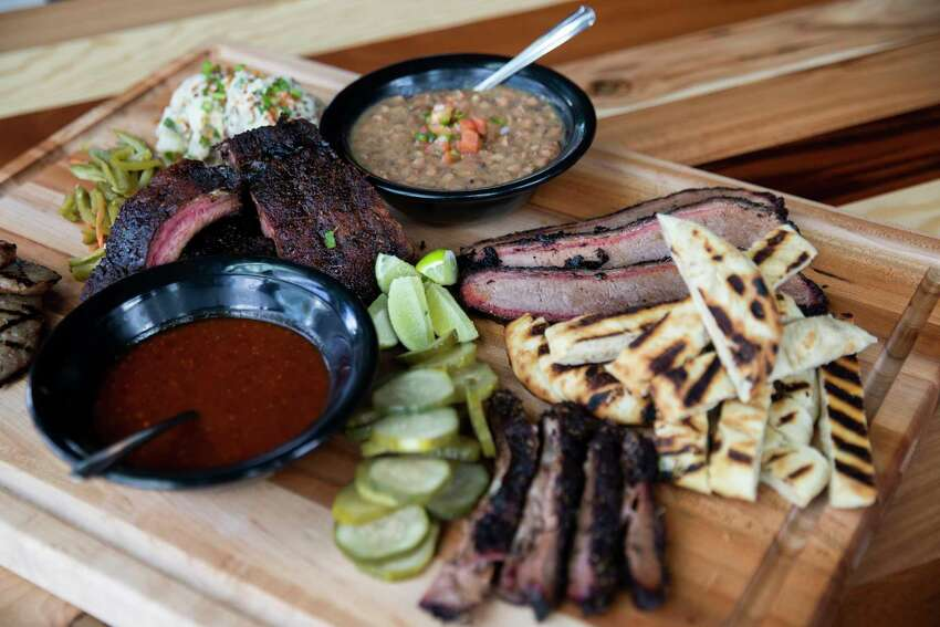 Woodshed Smokehouse's barbecue sampler includes sausage of the day, pork ribs, lamb brisket, beef brisket, sweet and spicy pickled, potatoes salad and borracho beans.