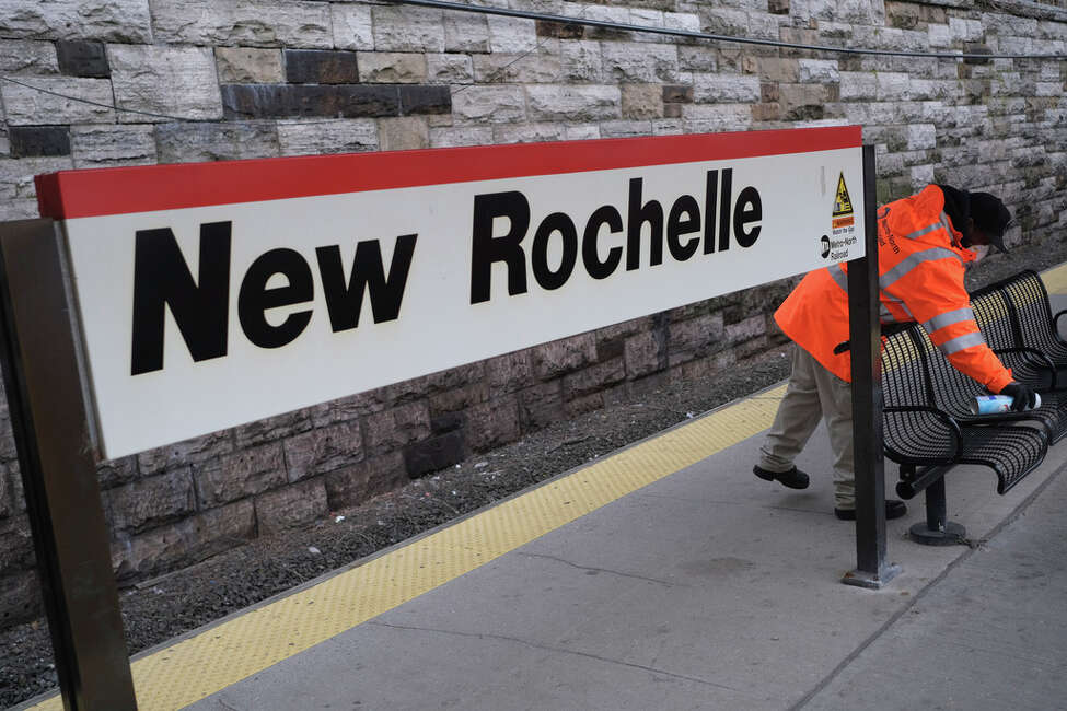Employees of Metro-North Railroad disinfect parts of the New Rochelle Metro-North station in New Rochelle, N.Y., Thursday, March 12, 2020. State officials are shuttering several schools and houses of worship for two weeks in the New York City suburb and sending in the National Guard to help with what appears to be the nation's biggest cluster of coronavirus cases, Gov. Andrew Cuomo said Tuesday.