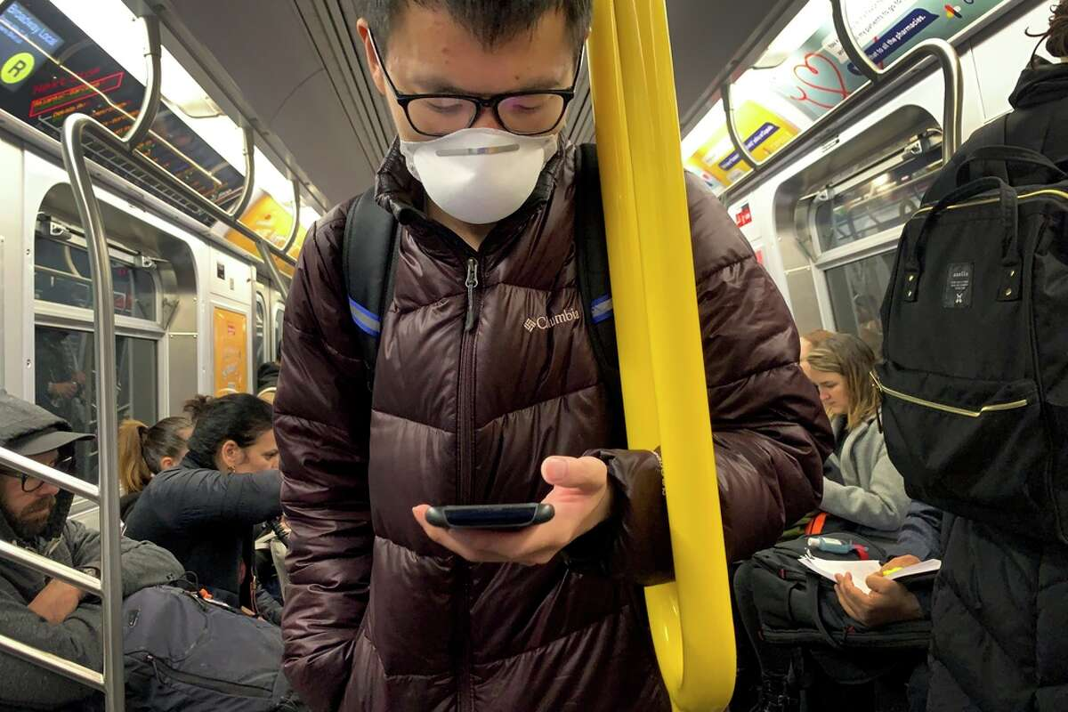 A commuter wears a mask while riding the subway at the start of a work day on Thursday, March 12, 2020, in the Brooklyn borough of New York. Mayor Bill de Blasio said Thursday he will announce new restrictions on gatherings to halt the spread of the new coronavirus in the coming days. The vast majority of people recover from the new coronavirus. According to the World Health Organization, most people recover in about two to six weeks, depending on the severity of the illness.