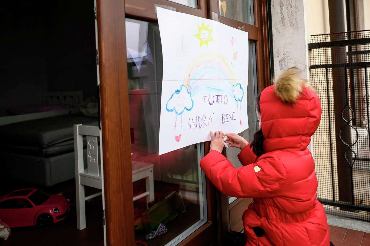 """A child tapes up at home a drawing she made, reading """"Everything is going to be alright"""", as part of school homeworks on the COVID-19 coronavirus on March 12, 2020 in Manta, near Cuneo, Northwestern Italy, as Italy shut all stores except for pharmacies and food shops in a desperate bid to halt the spread of a coronavirus that has killed 827 in the the country in just over two weeks. (Photo by MARCO BERTORELLO / AFP) (Photo by MARCO BERTORELLO/AFP via Getty Images)"""