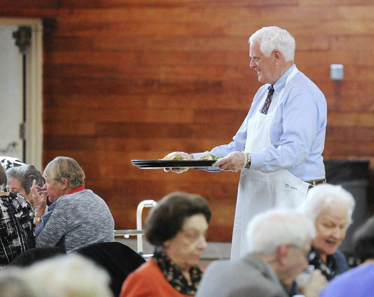 Greenwich Selectman John Toner serves a meal during the Greenwich Senior Center's annual Thanksgiving lunch party at the Eastern Greenwich Civic Center, Old Greenwich, Conn., Friday, Nov. 17, 2017. A traditional roasted turkey dinner was served by volunteers and Greenwich community leaders.