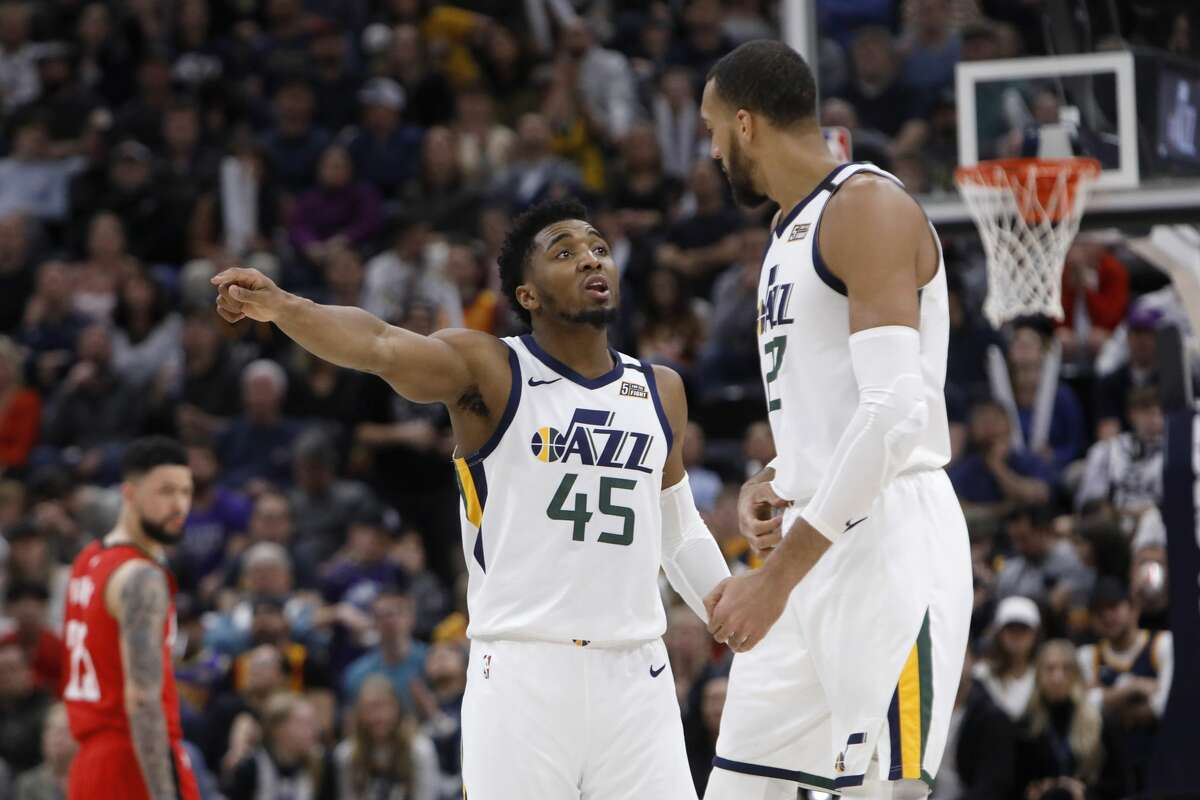 Utah Jazz's Donovan Mitchell (45) and Rudy Gobert talk during a time out in the second half during an NBA basketball game against the Houston Rockets on Saturday, Feb. 22, 2020, in Salt Lake City. The Houston Rockets defeated the Utah Jazz 120-110. (AP Photo/Kim Raff)