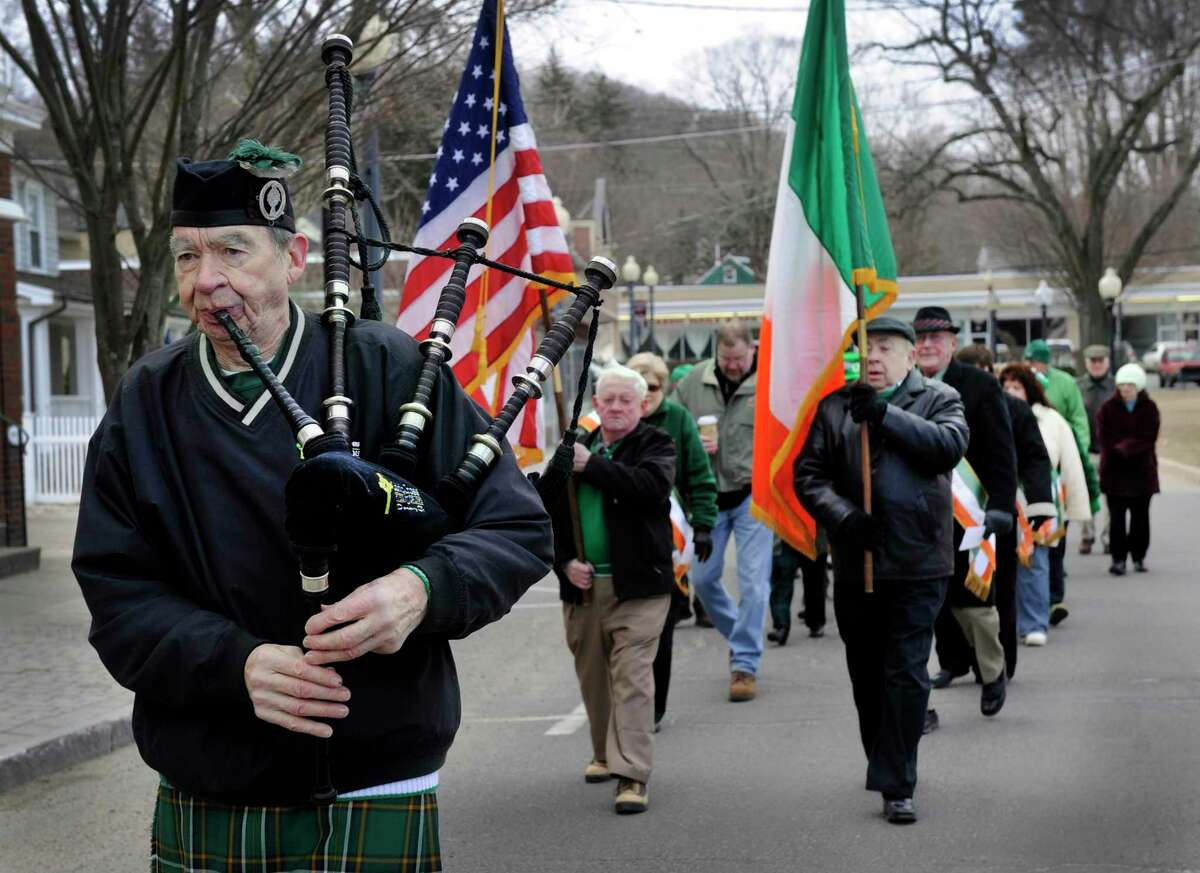 Peter Hearty of New Fairfield plays the bagpipes, Michael Keane of Danbury carries the American flag, and Jim Palardy of Bethel carries the Irish flag during a 2014 St. Patrick's Day parade.
