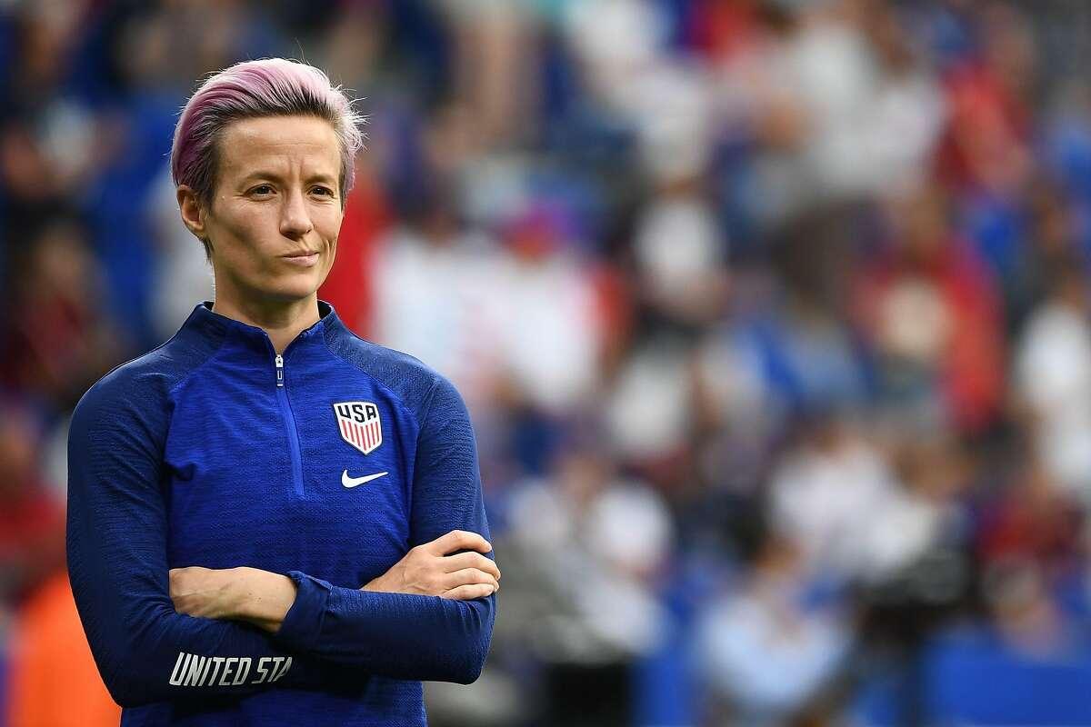 (FILES) In this file photo taken on July 02, 2019 United States' forward Megan Rapinoe looks on during warm up prior to the France 2019 Women's World Cup semi-final football match between England and USA, at the Lyon Satdium in Decines-Charpieu, central-eastern France. - Coca-Cola slammed on March 11, 2020, US Soccer after the federation claimed in court documents that playing for the men's national team carries more responsibility and requires a higher level of skill than that demanded of women players. (Photo by FRANCK FIFE / AFP) (Photo by FRANCK FIFE/AFP via Getty Images)
