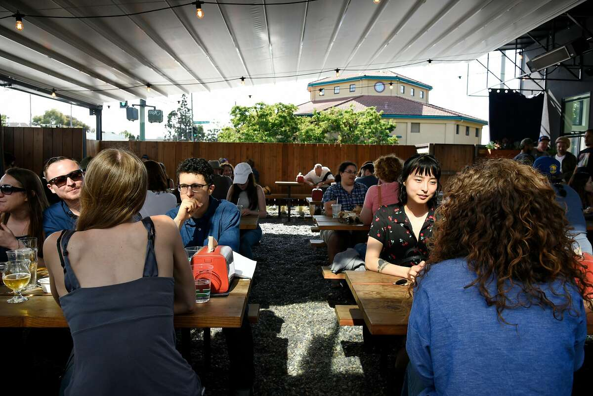 People sit under the retractable roof at Arthur Mac's Tap and Snack beer garden in Oakland, CA, on Saturday June 24, 2017.