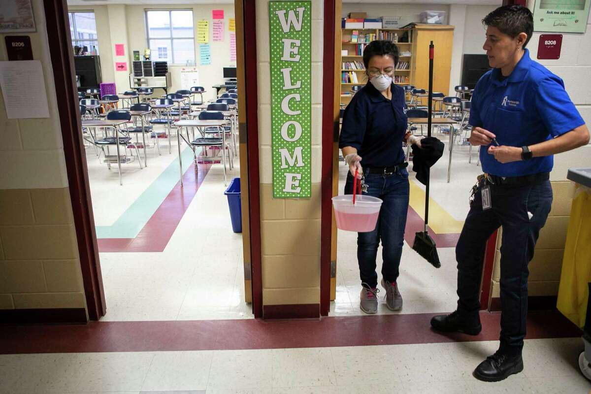 Mary Erazo, left, and Head Campus Custodian Patricia Avila, right, step out of a newly cleaned classroom at Dolph Briscoe Middle School early last March, as the coronavirus pandemic loomed.