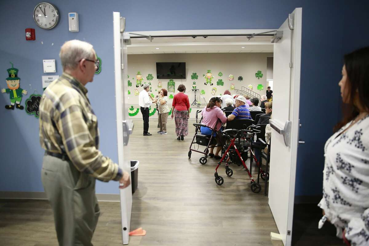 In this March 4, 2020, photo, seniors gather in an auditorium for morning announcements at Little Havana Activities and Nutrition Centers of Dade County, Inc., in Miami. The new coronavirus is posing a special challenge for nursing homes and other facilities that provide care for the elderly. (AP Photo/Brynn Anderson)