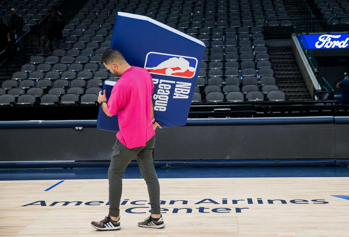 Crews break down the court after the Dallas Mavericks beat the Denver Nuggets 113-97 on Wednesday, March 11, 2020 at American Airlines Center in Dallas. During the game, the NBA suspended all games due to the spread of the new coronavirus. (Ashley Landis/The Dallas Morning News/TNS)
