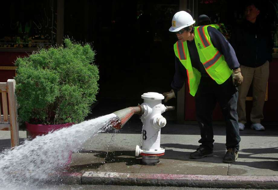 A worker flushes water from the line after replacing a fire hydrant. Photo: Hearst Connecticut Media / ONLINE_YES