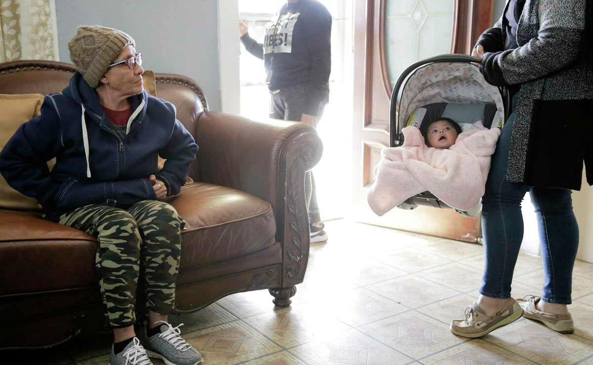 Manchester neighborhood resident Maria Cruz looks at her granddaughter, Madison, inside her home on Thursday, Dec. 19, 2019.