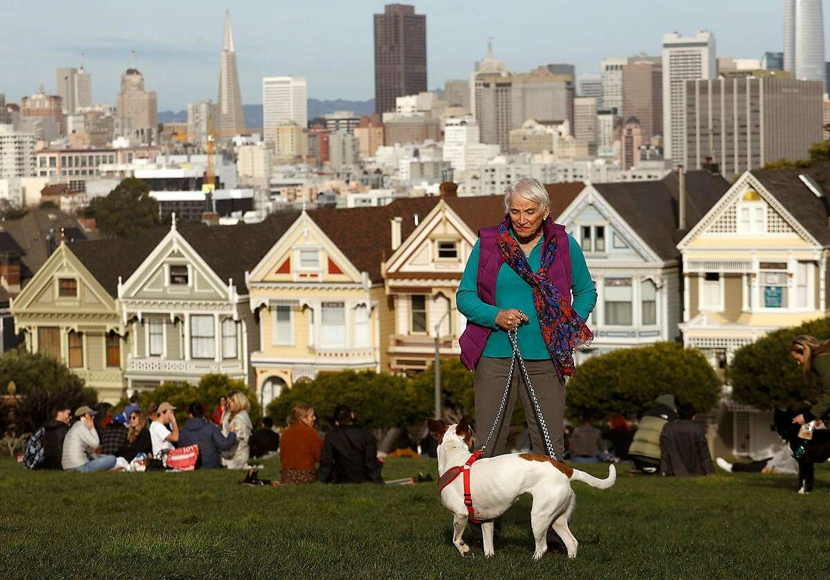 """Transgender activist Roberta """"Bertie"""" Brouhard, 73, visits Alamo Square with her dog Lea against a backdrop of the famed Victorian homes called, """"The Painted Ladies."""""""
