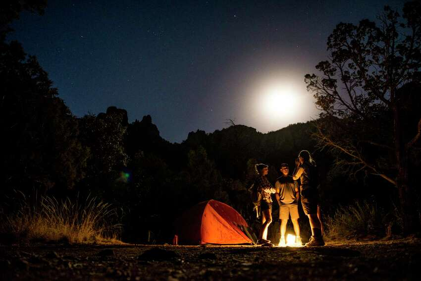 Big Bend National Park Backpackers talk around a lantern as a full moon rises in the Chisos Basin at Big Bend National Park. Another stargazer paradise as it's also a great place to catch the annual Lyrids meteor shower and a great opportunity to celebrate International Dark Sky Week each year.