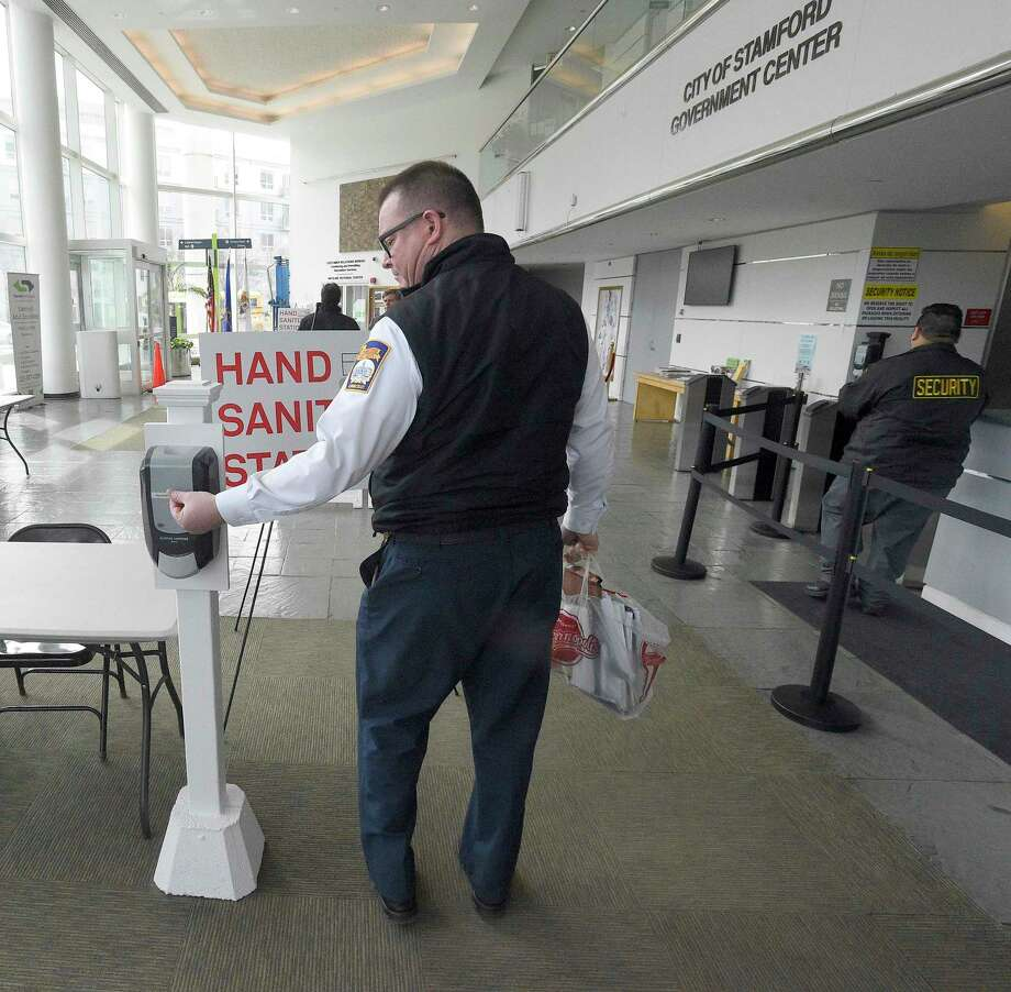 A city employee uses a hand sanitizer station as they enter the Stamford Government Center on Wednesday. Photo: Matthew Brown / Hearst Connecticut Media / Stamford Advocate