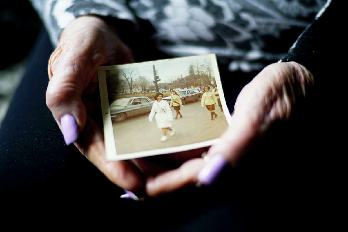 Alice Burke holds a photo of herself marching in the Albany St. Patrick's Day Parade in 1969 at her home on Thursday, March 12, 2020, in Colonie, N.Y. Burke has marched in the parade for the last 55 years. (Paul Buckowski/Times Union)