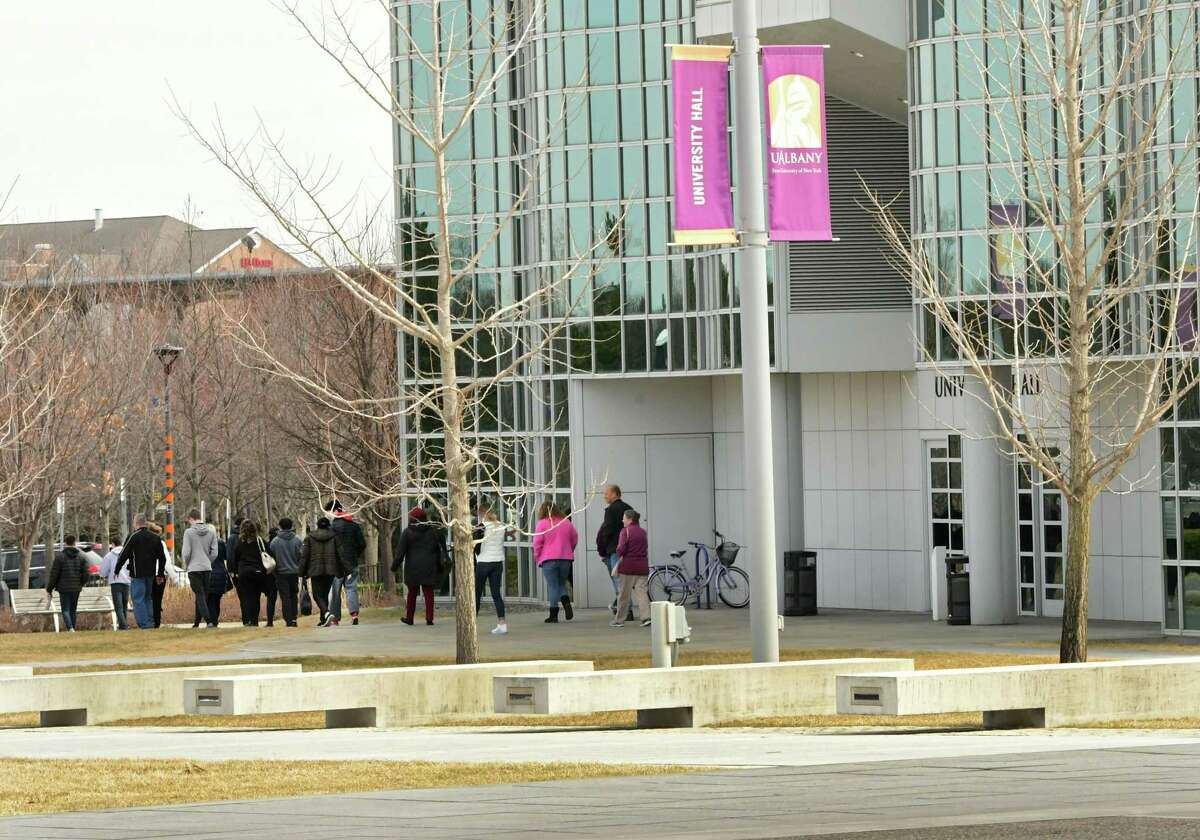 A mass of people are seen walking out of University Hall at University at Albany on Thursday, March 12, 2020 in Albany, N.Y. The school is taking precautions due to a coronavirus case. (Lori Van Buren/Times Union)