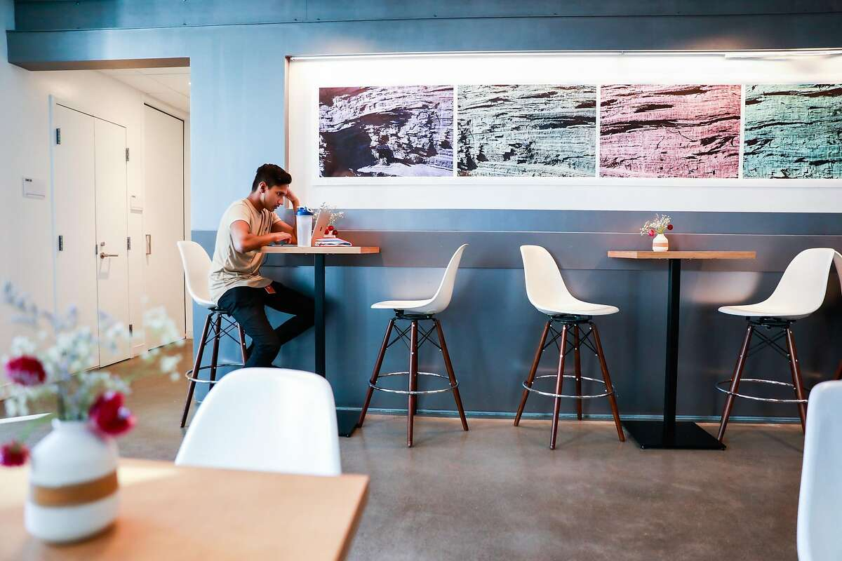 Imesh Samarakoon works at Andytown coffee in a largely empty space in SOMA on Wednesday, March 11, 2020 in San Francisco, California. The coffee shop would normally be packed during the day. The coronavirus has impacted many businesses because people have been told to work from home.