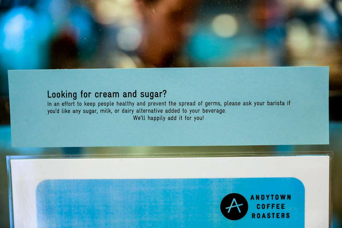 A note is posted at Andytown coffee advising customers come to the counter to add milk or sugar as a way to avoid spreading germs on Wednesday, March 11, 2020 in San Francisco, California. The coronavirus has impacted many businesses because people have been told to work from home.
