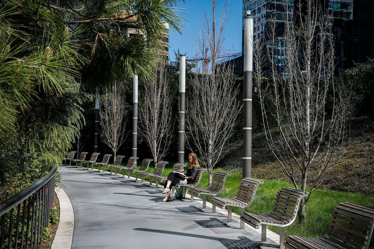 Meghan Michael reads a book on a bench at Salesforce Park which was significantly quieter than normal on Wednesday, March 11, 2020 in San Francisco, California. The coronavirus has impacted many areas because people have been advised by their companies to work from home.