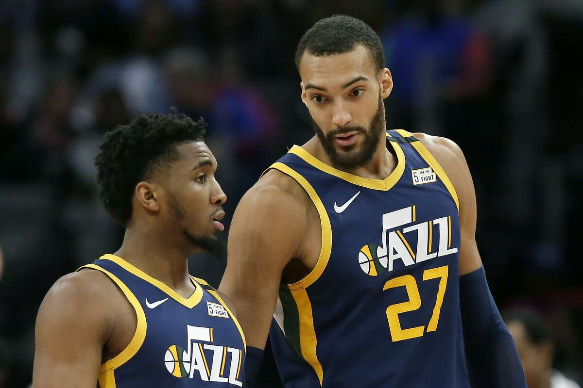 Utah Jazz center Rudy Gobert (27) talks with guard Donovan Mitchell, left, during the second half of an NBA basketball game against the Detroit Pistons Saturday, March 7, 2020, in Detroit. (AP Photo/Duane Burleson)