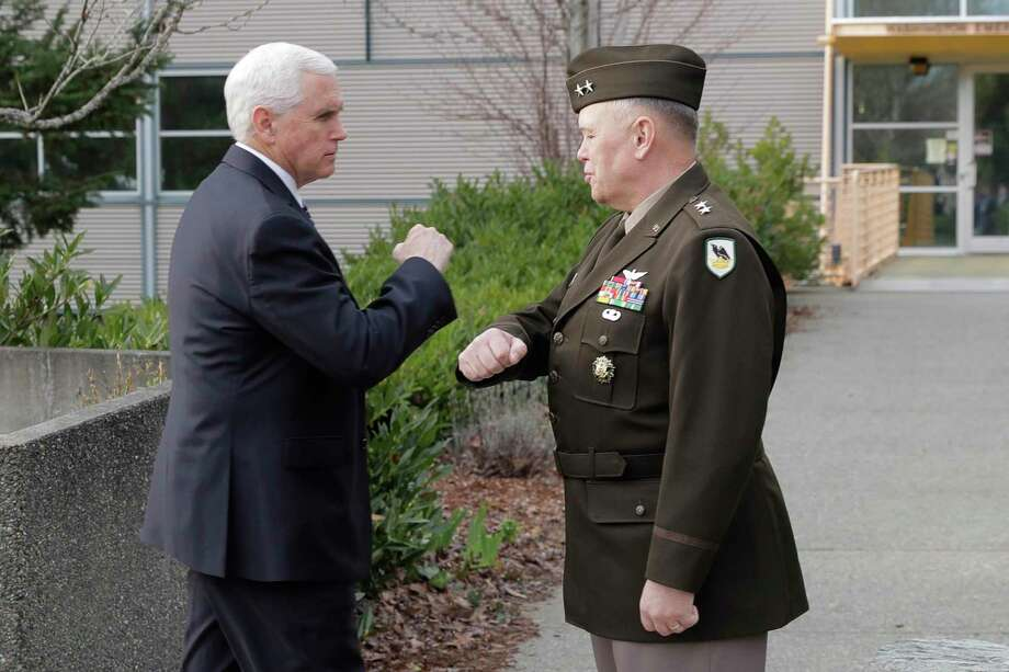 Vice President Mike Pence, left, bumps elbows with Maj. Gen. Bret Daugherty, right, Adjutant General of Washington State, before a tour of the Washington State Emergency Operations Center, Thursday, March 5, 2020 at Camp Murray in Washington state to discuss the COVID-19 coronavirus. Officials are avoiding shaking hands as a precaution against the virus. (AP Photo/Ted S. Warren) Photo: Ted S. Warren / Ted S. Warren / Associated Press / Copyright 2020 The Associated Press. All rights reserved.
