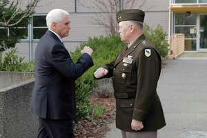 Vice President Mike Pence, left, bumps elbows with Maj. Gen. Bret Daugherty, right, Adjutant General of Washington State, before a tour of the Washington State Emergency Operations Center, Thursday, March 5, 2020 at Camp Murray in Washington state to discuss the COVID-19 coronavirus. Officials are avoiding shaking hands as a precaution against the virus. (AP Photo/Ted S. Warren)