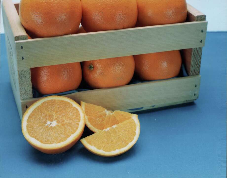 Sliced orange and a small wooden crate of oranges. Photo: COURTESY PHOTO