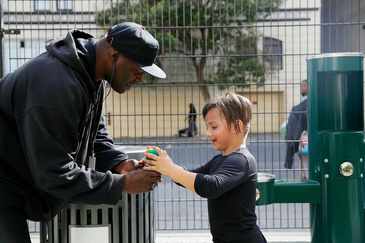 Dewayne Kemp, Urban Alchemy supervisor, assists Carlitos Vasquez, 6, with his snow cone as Kemp works and Vasquez plays at the new Turk and Hyde Mini Park on Thursday, March 5, 2020 in San Francisco, Calif.