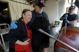 Rich Courville gets a thank you hug from Linda Domino as they and others begin cooking the first batches of tomato gravy for the upcoming St. Joseph Day festival at St. Anthony Cathedral Basilica. Courville and staff spent Sunday morning and afternoon cooking up 150 gallons of gravy to be served with pasta at the annual event, which runs on March 19. Photo taken Sunday, March 8, 2020 Kim Brent/The Enterprise