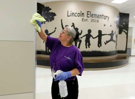 Custodian Ranae Cox works to clear Lincoln Elementary School, Thursday, March 12, 2020, in Montgomery. Members of Montgomery ISD's service for education management began additional disinfectant steps at all of the district's 10 schools. Superintendent Beau Rees announced the district would close two days ahead of spring break in an abundance of caution after health officials announced Montgomery County's first 'presumptive positive' case of the coronavirus on March 11.