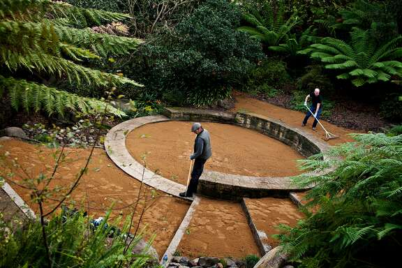 Ray Goodenough, left, a gardener with Recreation and Park, and Tom Jensen, co-chair of the National AIDS Memorial Grove board, rake freshly thrown dirt at the restored waterfall memorial while preparing for a celebration of the 20th anniversary of the grove on December 1 in Golden Gate Park, Monday, November 28, 2011.   Jason Henry/Special to The Chronicle