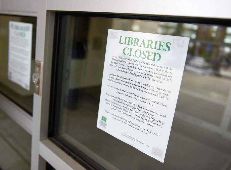 Signs notify the public that Greenwich Library is closed due to the threat of the coronavirus in Greenwich, Conn. Thursday, March 12, 2020. Library members are told not to return their books in the book drops, as the due date for all materials will be extended indefinitely. Photo: Tyler Sizemore / Hearst Connecticut Media / Greenwich Time