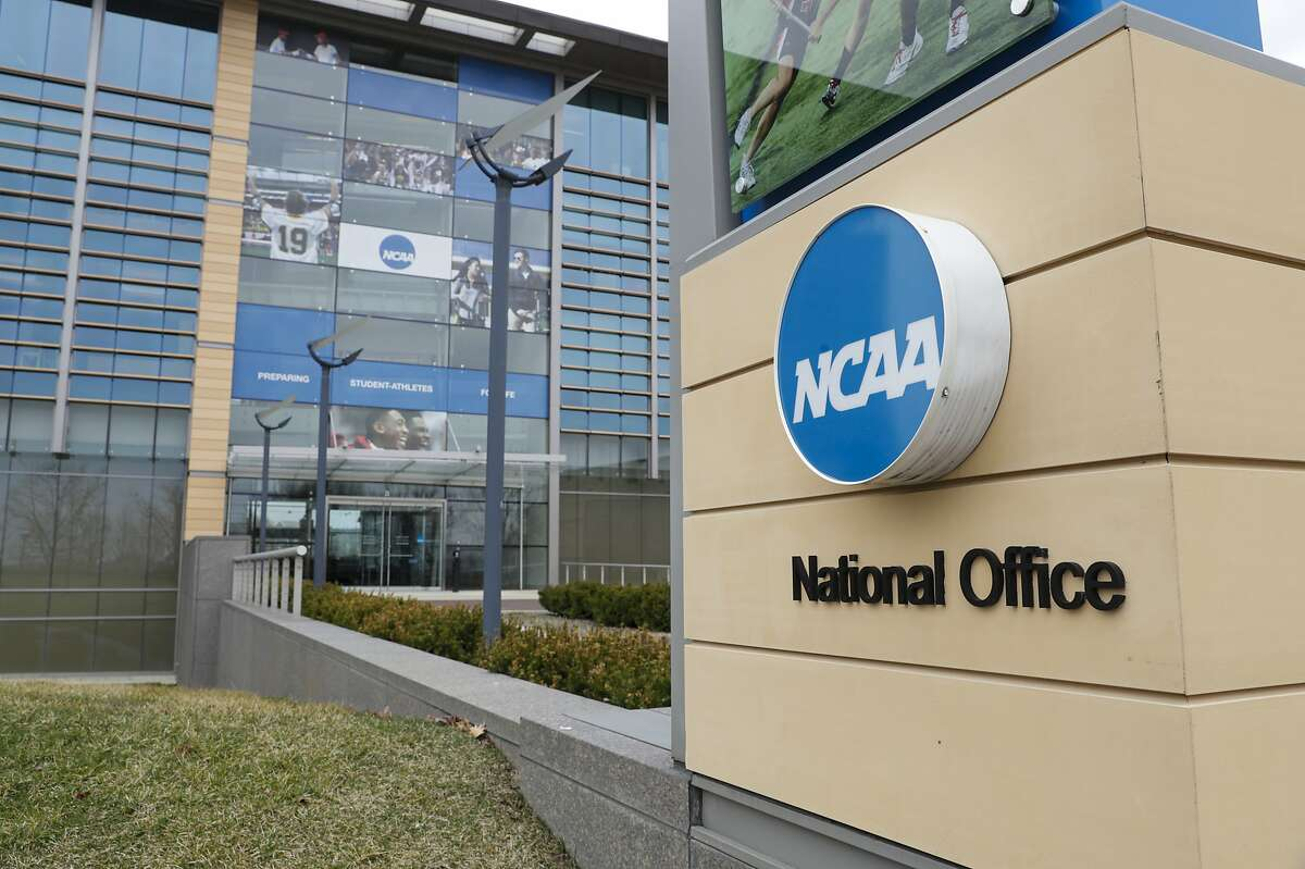 Final Four flag fly over the headquarter of the NCAA in Indianapolis, Thursday, March 12, 2020. (AP Photo/Michael Conroy)